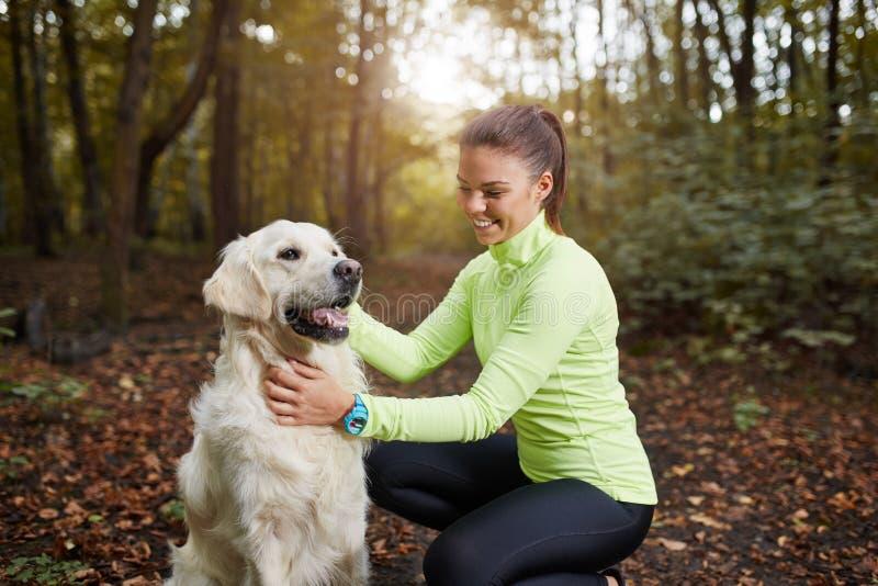 Ung idrottskvinna och hennes hund arkivfoto
