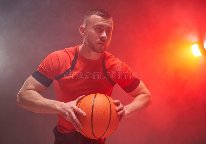 Ung idrottsman, basketbollspelare som förbereder sig för att kasta bollen med bakljus och rök i bakgrunden royaltyfria bilder