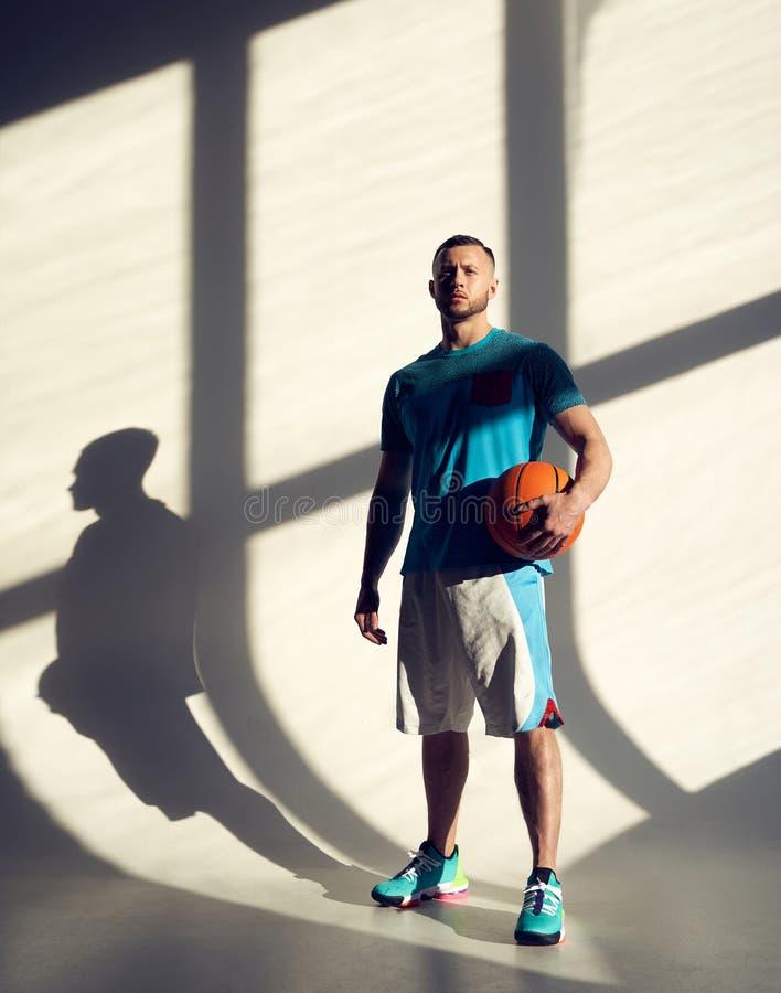 Ung idrottsman, basketbollspelare som håller bollen och står nära väggen med skuggor från fönster arkivfoton