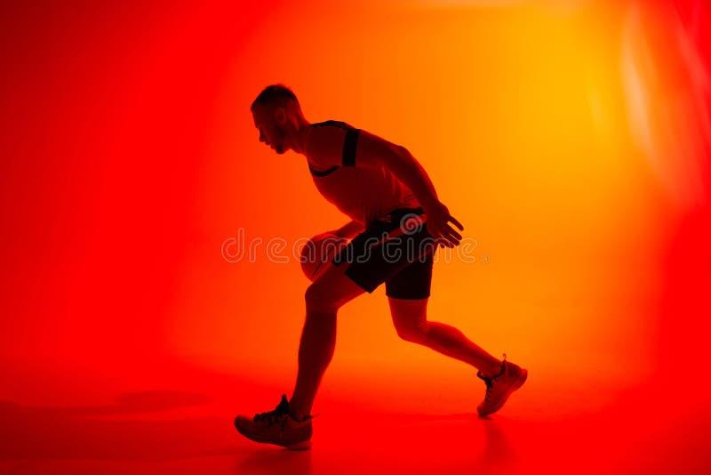 Ung idrottsman, basketbollspelare som kör med boll på röd och orange bakgrund arkivfoto