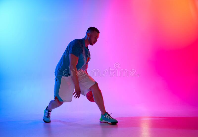 Ung idrottsman, basketbollspelare som springer med boll på nyblå och rosa bakgrund royaltyfri bild