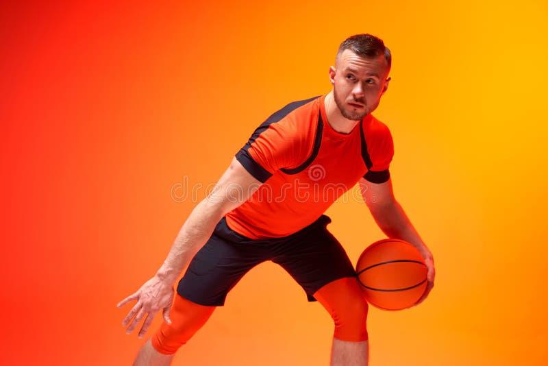 Ung idrottsman, basketbollspelare som står med kulan i försvarsposition på orange och röd bakgrund arkivbilder