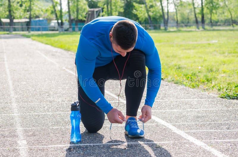 Ung idrottsman nen i hörlurar, bundna sportskor royaltyfria foton