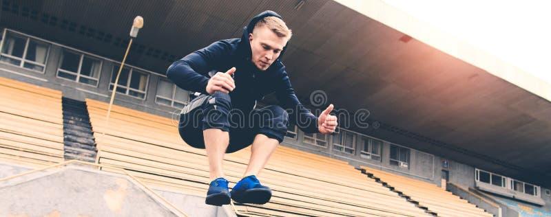 Ung idrottsman nen som hoppar över häck under genomkörare på stadion arkivbilder