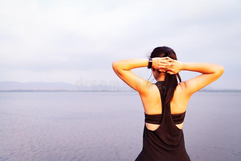 Ung idrottsman nenkvinna som streching nära utomhus- asiatiskt för kondition gå för sjö och övning i solnedgångplats wellness och arkivbild