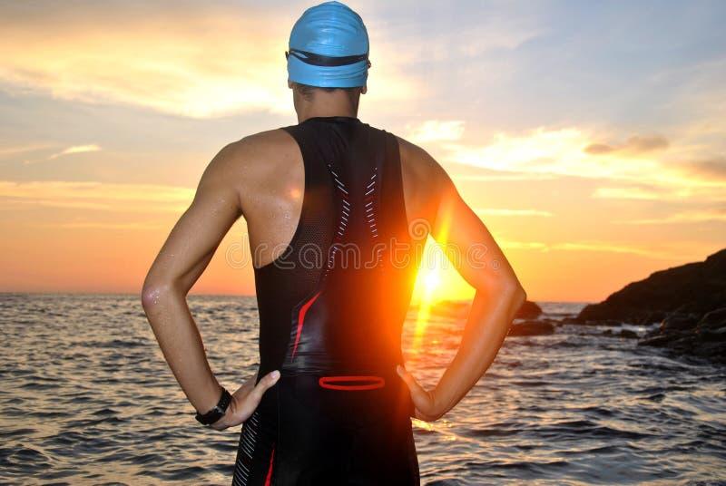 Ung idrottsman nentriathlon framme av en soluppgång royaltyfri foto