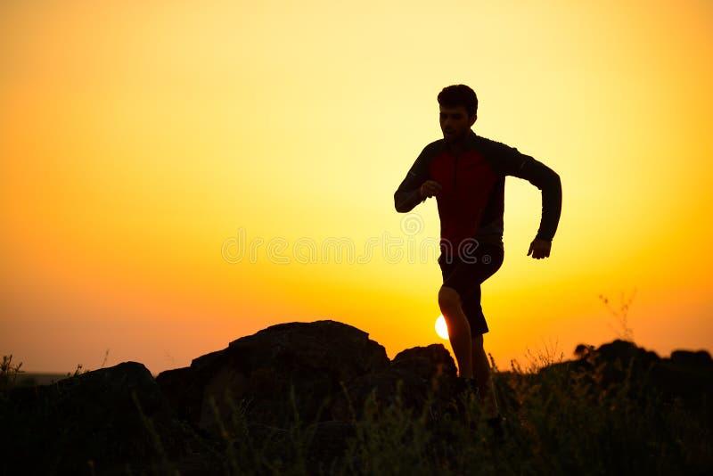 Ung idrottsmanspring på Rocky Mountain Trail på solnedgången aktiv livsstil royaltyfri fotografi