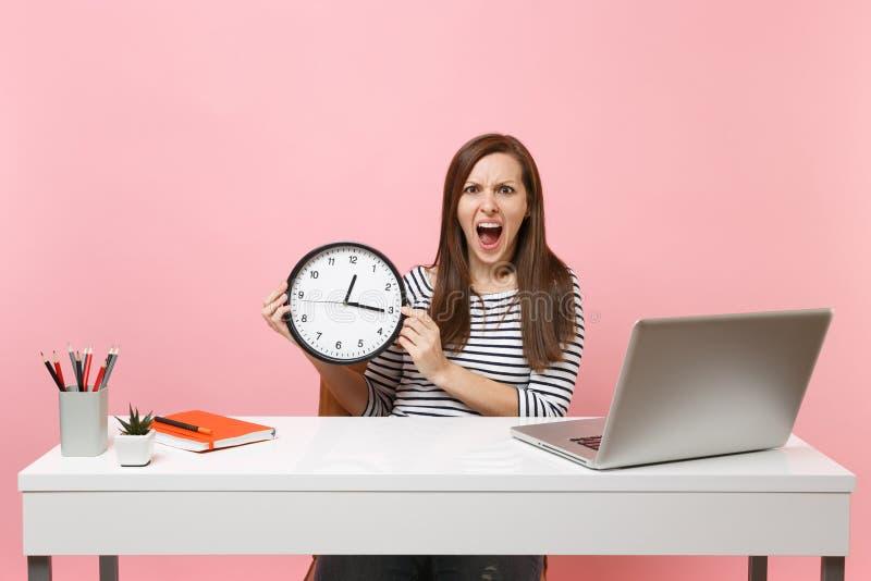 Ung ilsken kvinna som rymmer den runda ringklockan som skriker, medan sitt arbete på kontoret med den isolerade PCbärbara datorn  arkivfoto