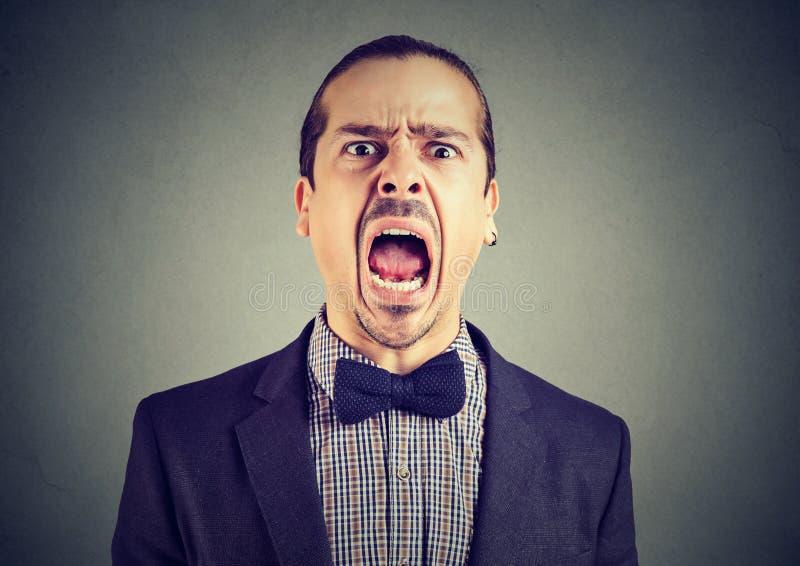 Ung ilsken man som skriker med den öppna munnen för sned boll royaltyfri fotografi