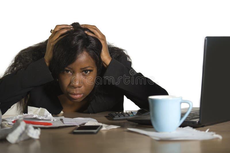 Ung ilsken och uppriven svart afrikansk amerikanaffärskvinna som arbetar i spänning på desperat känsla för skrivbord för kontorsd arkivfoto