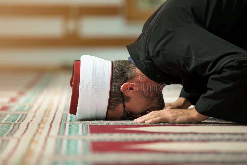 Ung Imam som ber inom av härlig moské arkivfoto