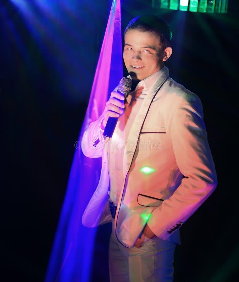 Ung impressario med en mikrofon i en nattklubb royaltyfria foton