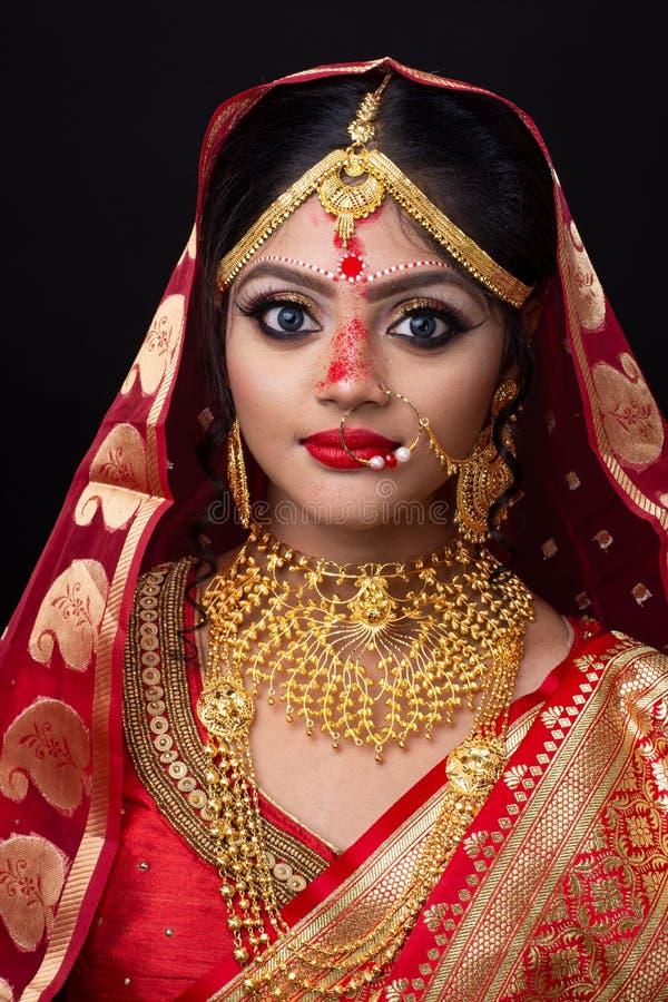 Ung indisk brud i röd sari och guld- smycken royaltyfria foton