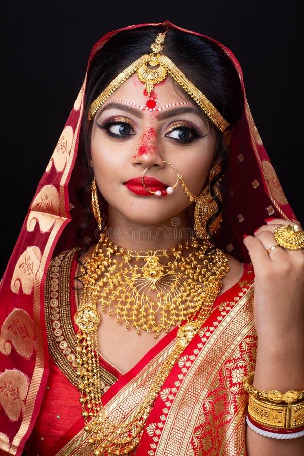 Ung indisk brud i röd sari och guld- smycken arkivfoton