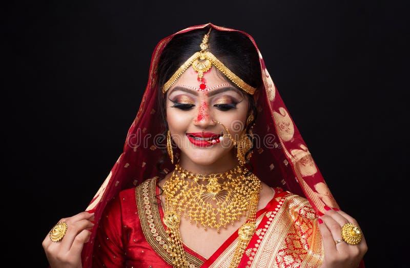 Ung indisk brud i röd sari och guld- smycken med ögonmakeup royaltyfria foton