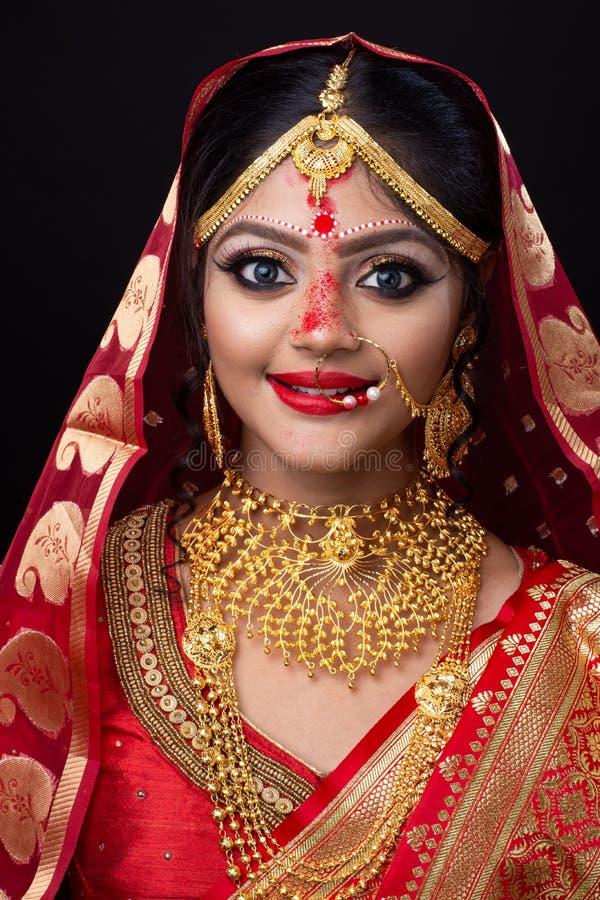 Ung indisk brud i röd sari och guld- smycken med ögonmakeup arkivbilder