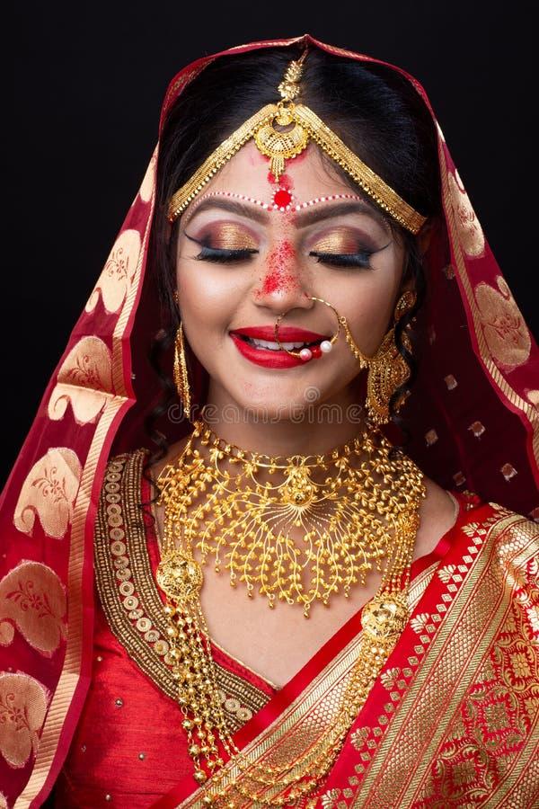 Ung indisk brud i röd sari och guld- smycken med ögonmakeup royaltyfri fotografi