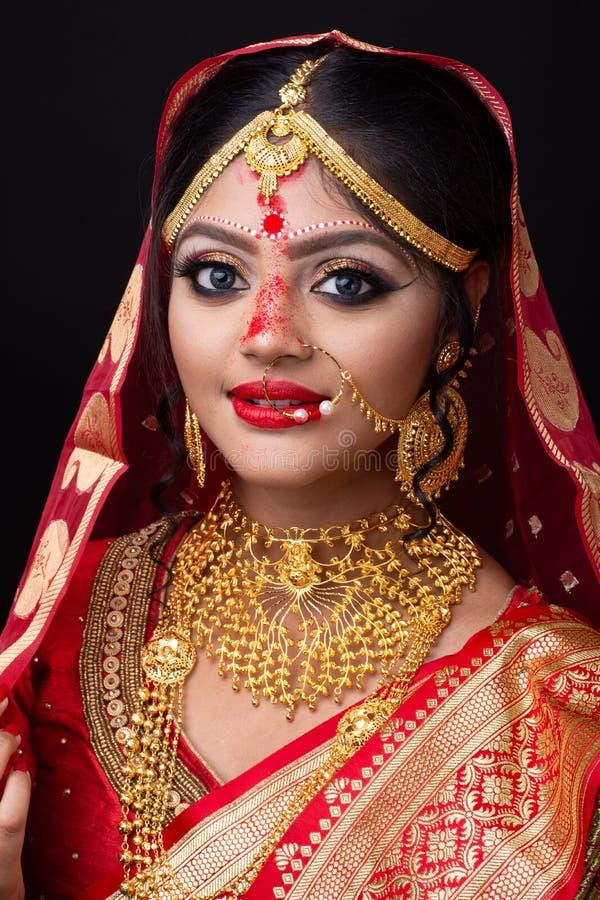 Ung indisk brud i sari och guld- smycken royaltyfri bild