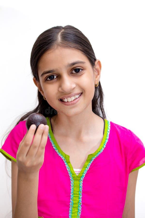 Ung indisk flicka som äter en gulabjamun - en indisk sötsak arkivfoto