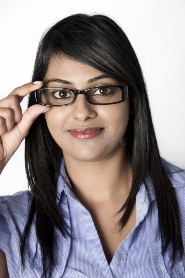 Ung indisk kvinna med inramade exponeringsglas som ler royaltyfri fotografi