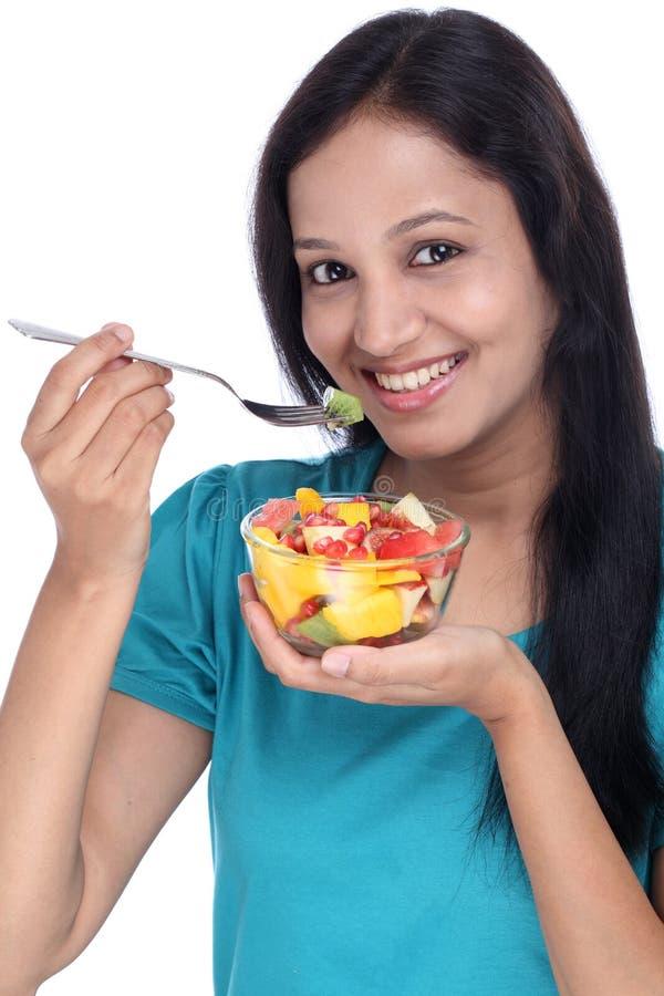 Ung indisk kvinna som äter fruktsallad royaltyfri fotografi