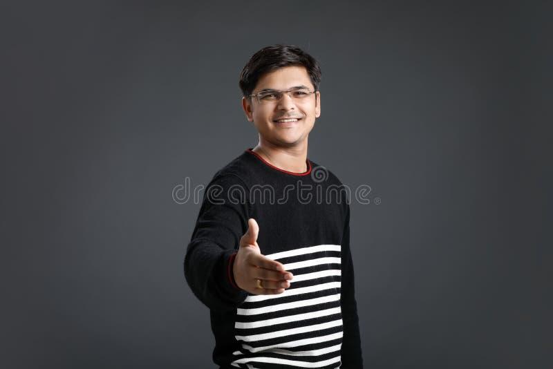 Ung indisk man som över gör ett avtal royaltyfri foto