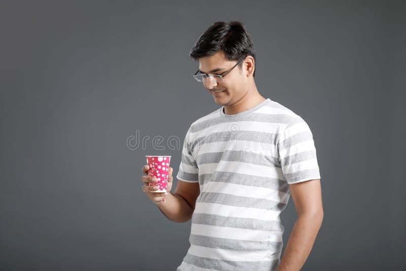 Ung indisk man som dricker ett vatten royaltyfri bild