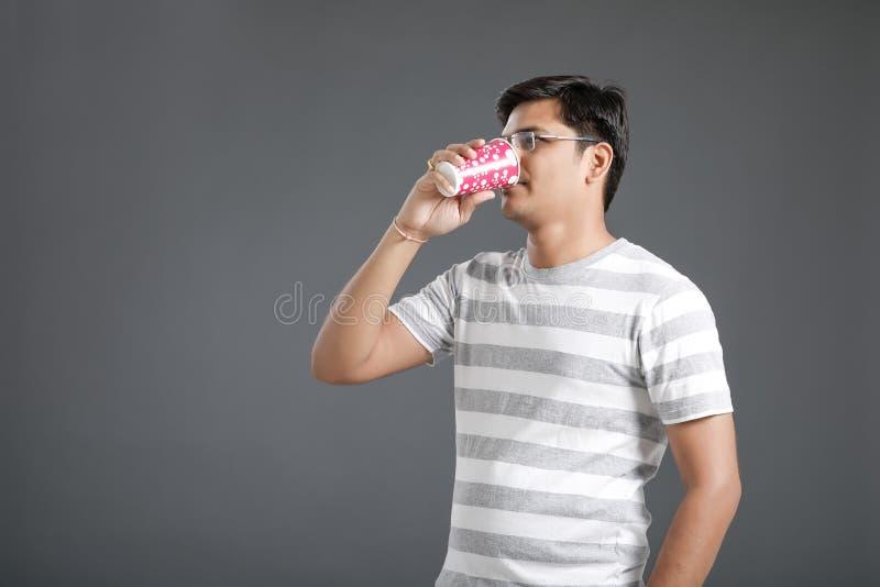 Ung indisk man som dricker ett vatten royaltyfri foto