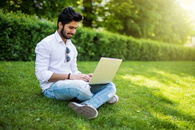 Ung indisk studentman med en bärbar dator som sitter på gräset stads- stil fotografering för bildbyråer