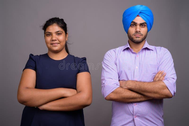 Ung indiska par tillsammans och förälskat med korsade armar arkivbild