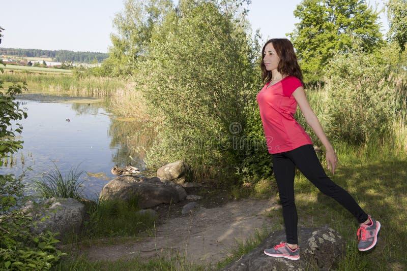 Ung joggerkvinna som sträcker i natur arkivbilder