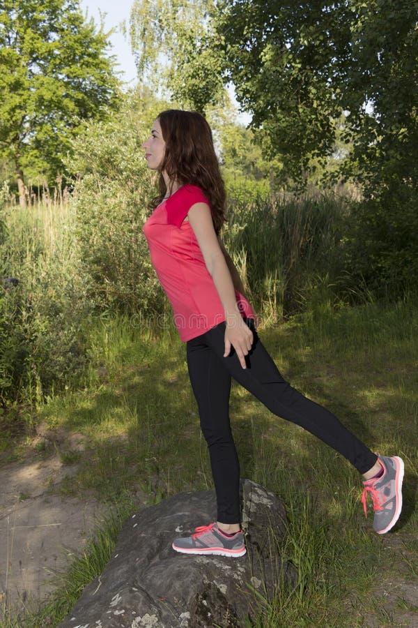 Ung joggerkvinna som sträcker i natur efter sportar royaltyfri bild