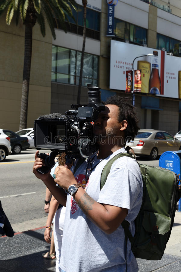 Ung kameraman som använder en yrkesmässig camcorder royaltyfri fotografi