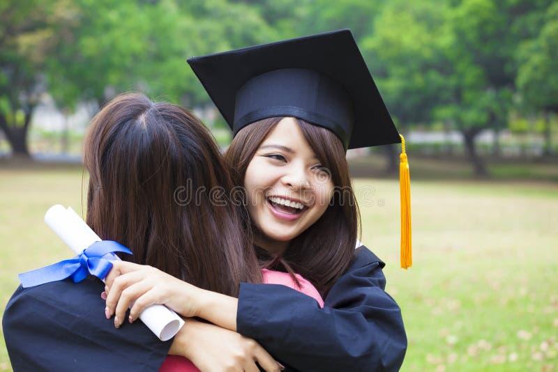 Ung kandidat som kramar hennes vän på avläggande av examenceremoni royaltyfri bild