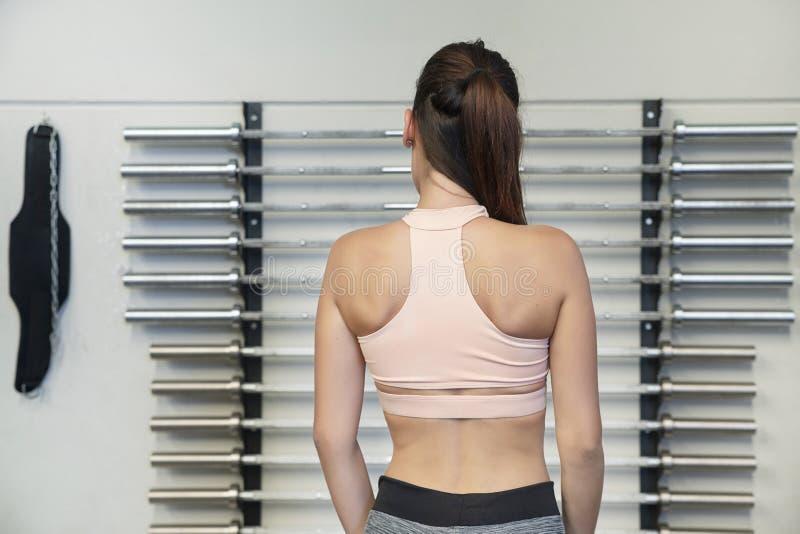 Ung kaukasisk kvinna som visar toning och definition på gymmet eller en träningsstudio arkivbild