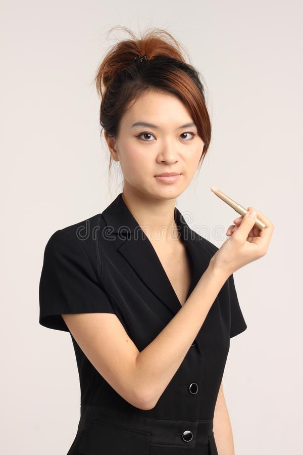 Ung kinesisk dam i formell dress som får klar till kontoret royaltyfri bild