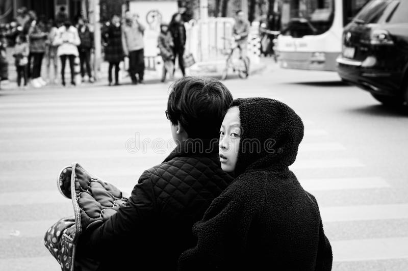 Ung kinesisk flicka med en svart huv på sparkcykeln arkivfoto