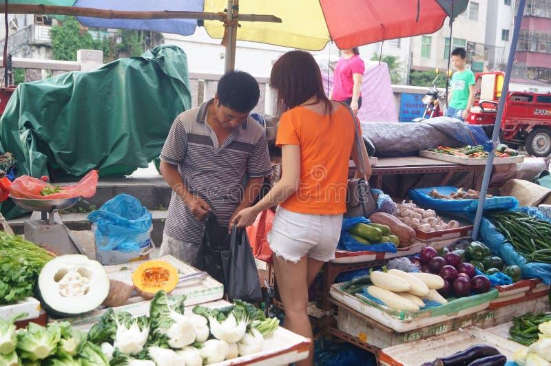 Ung kinesisk flicka på bönders marknad som köper grönsaker royaltyfria foton