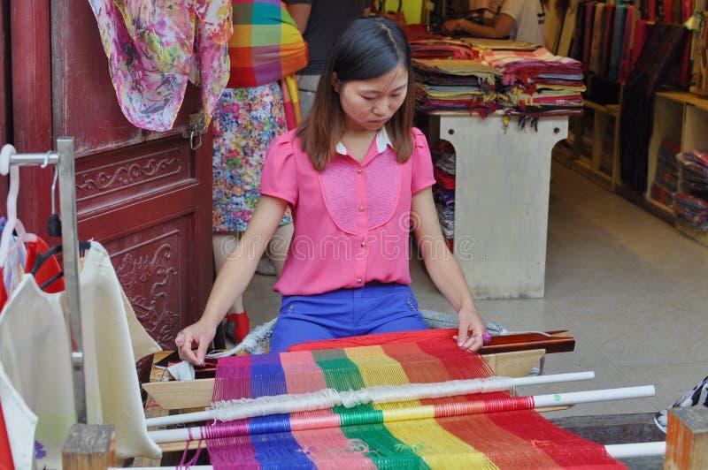 Ung kinesisk kvinna som arbetar på en vävstol som väver en röd halsduk fotografering för bildbyråer