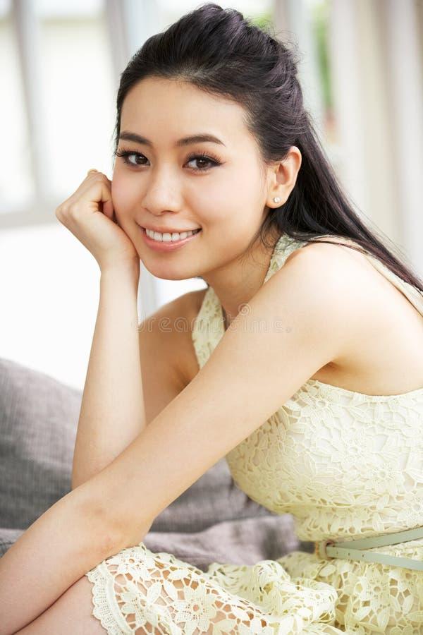 Ung kinesisk kvinna som hemma kopplar av på sofaen royaltyfria bilder