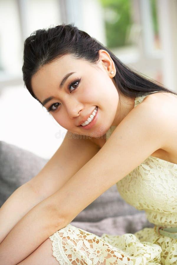 Ung kinesisk kvinna som hemma kopplar av på sofaen fotografering för bildbyråer