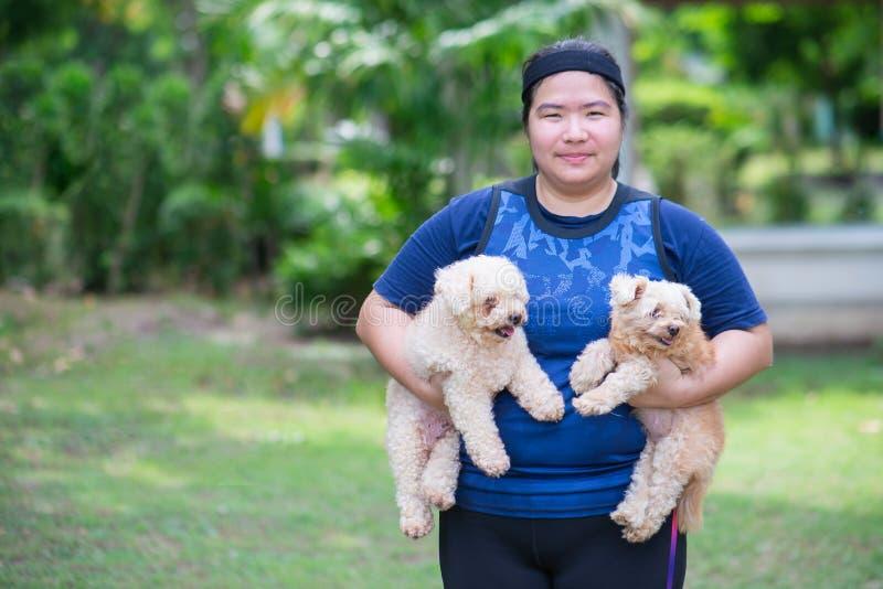 Ung kinesisk kvinnadet fria som rymmer hunden royaltyfri fotografi