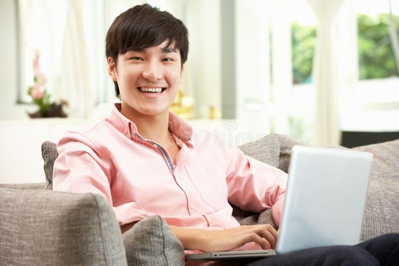 Ung kinesisk man som använder att koppla av för bärbar datorstund royaltyfri fotografi