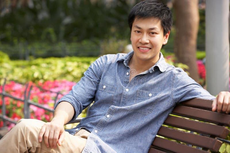 Ung kinesisk man som kopplar av på Parkbänk arkivbilder