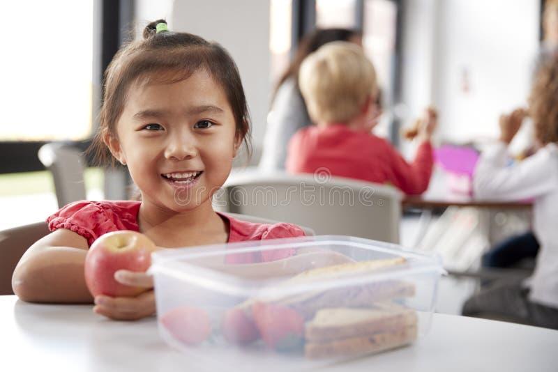 Ung kinesisk skolflicka som sitter på en tabell under hennes lunchavbrott på dagiset som rymmer ett äpple och ler, slut upp royaltyfria foton