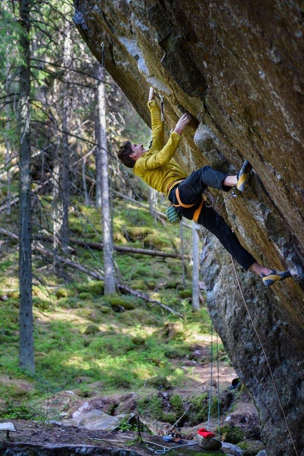 Ung klättrareman som klättrar en vagga Nordeuropa loppdestin royaltyfri fotografi