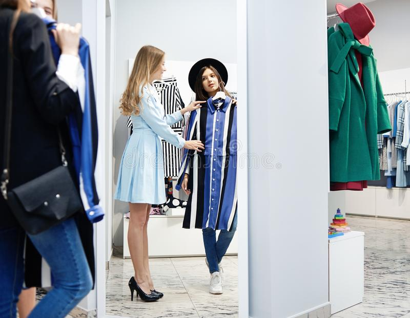 Ung klient som försöker på klänningen i shoppa fotografering för bildbyråer