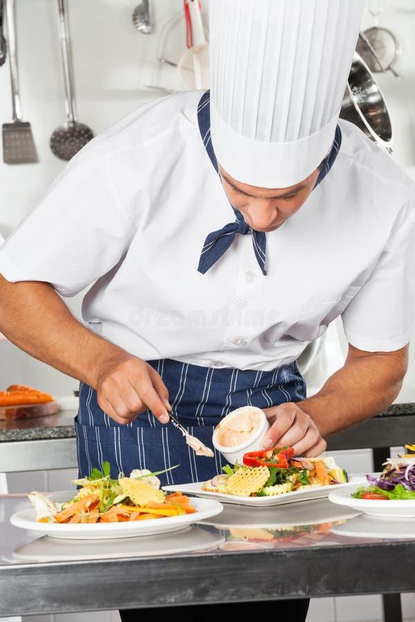Kock som garnerar maträtten med Mayonnaise arkivbilder