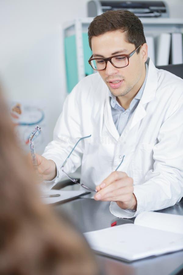Ung kompetent ögonläkare som talar till den kvinnliga patienten royaltyfri foto