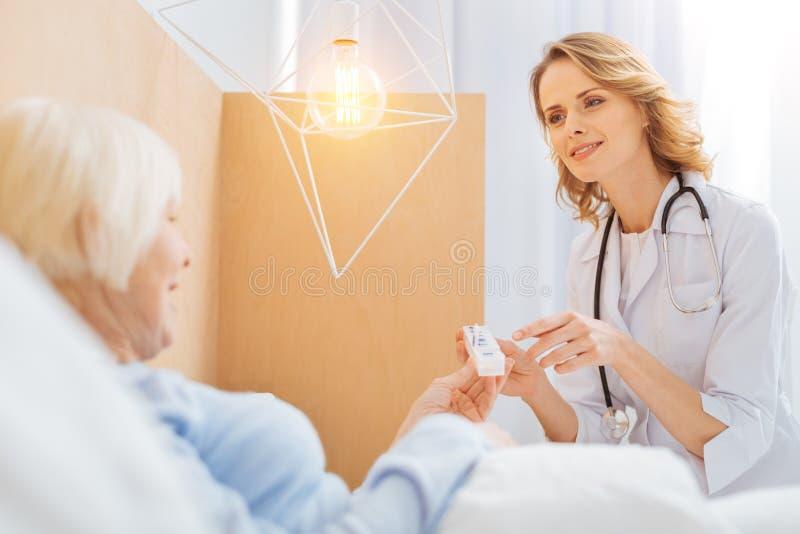 Ung kompetent doktor som ler till hennes patient arkivbild